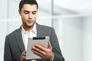 bigstock-Handsome-man-using-his-tablet--51559894